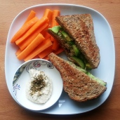 tuna salad sandwich with avocado and cucumber, carrots and hummus with dukkah spice